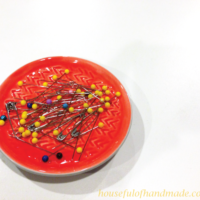 Coral colored ring dish turned into a DIY magnetic pin cushion.
