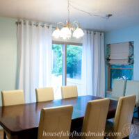 Dining room with blue painted walls and white thin curtains with grommets around a sliding glass door.