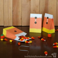 Three paper treat bags with ikat candy corn design on them filled with fall candy.