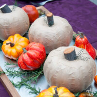 Three rustic pumpkins made from dollar store pumpkins on a tray for a centerpiece.
