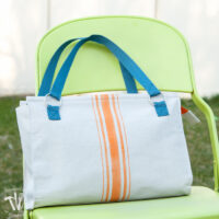Handmade purse made from drop cloth with orange painted grain sack stripes and blue handles.