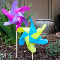 Two DIY giant outdoor pinwheels, one with pink and purple vanes and the other with blue and green, stuck in a flower garden.