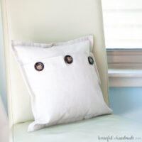 Pillow cover made from drop cloth with three buttons fold over closure.