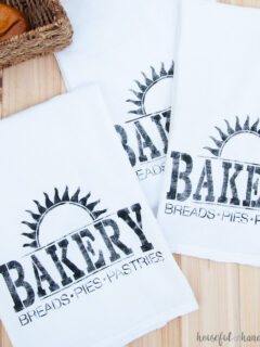 Three tea towels painted with a stencil to say Bakery with a sun burst above it.