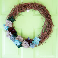 Grapevine wreath with succulents made out of colored leathers on it hanging on a green door.