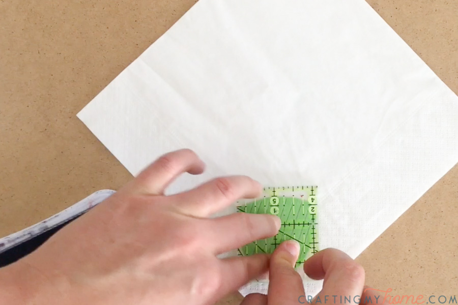 Placing the stamp on the corner of the disposable napkin.