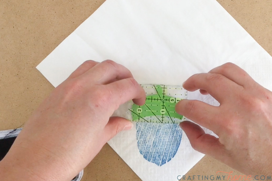 Placing the stamp for top of the acorn design on the decorative napkin.