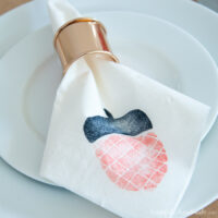 Acorn stamped decorative napkin in a rose gold napkin ring on a white plate.