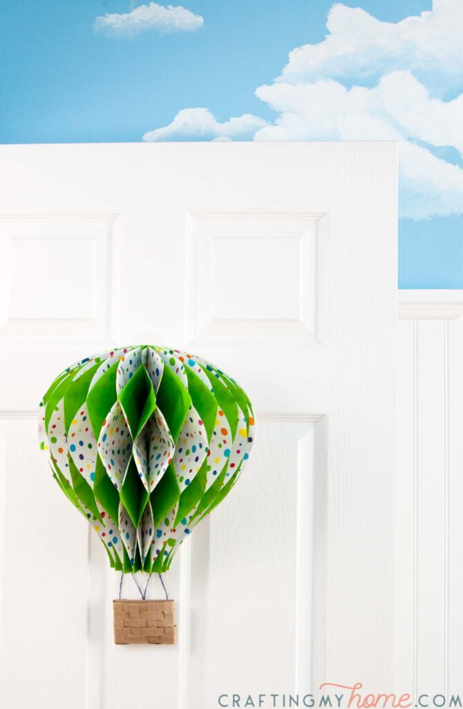Hot air balloon decor hanging on a door with a sky painted wall behind it.