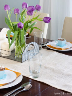 Spring tablescape with white burlap runner, tulips, bunnies, and paper tea cups.