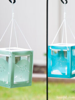 Two coastal themed wood lanterns hanging on a hook in the yard with solar lanterns inside.