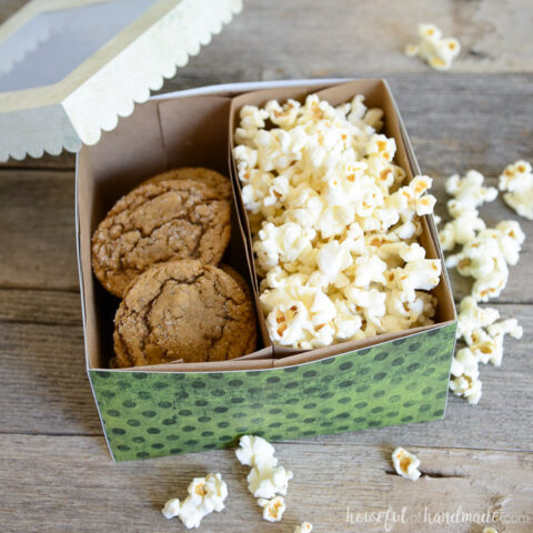Green dotted paper cookie box with 2 compartments inside, one filled with cookies and the other with popcorn, with the lid sitting on the egde.