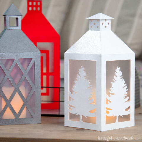 Three paper lanterns with flameless candles inside sitting on a table.