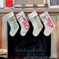 Four DIY personalized Christmas stockings made from drop cloth, two with bows on top and two with fur.