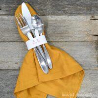 Bunny napkin ring around a napkin with silverware tucked inside.