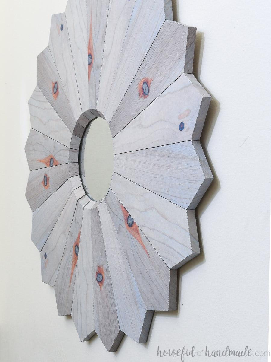 Sideways view of the 3D paper wall mirror that looks like a wood sunburst mirror.