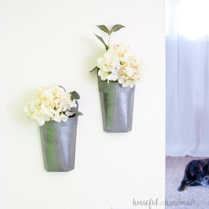 White wall with faux metal wall vases hanging on it, filled with white hydrangea flowers.