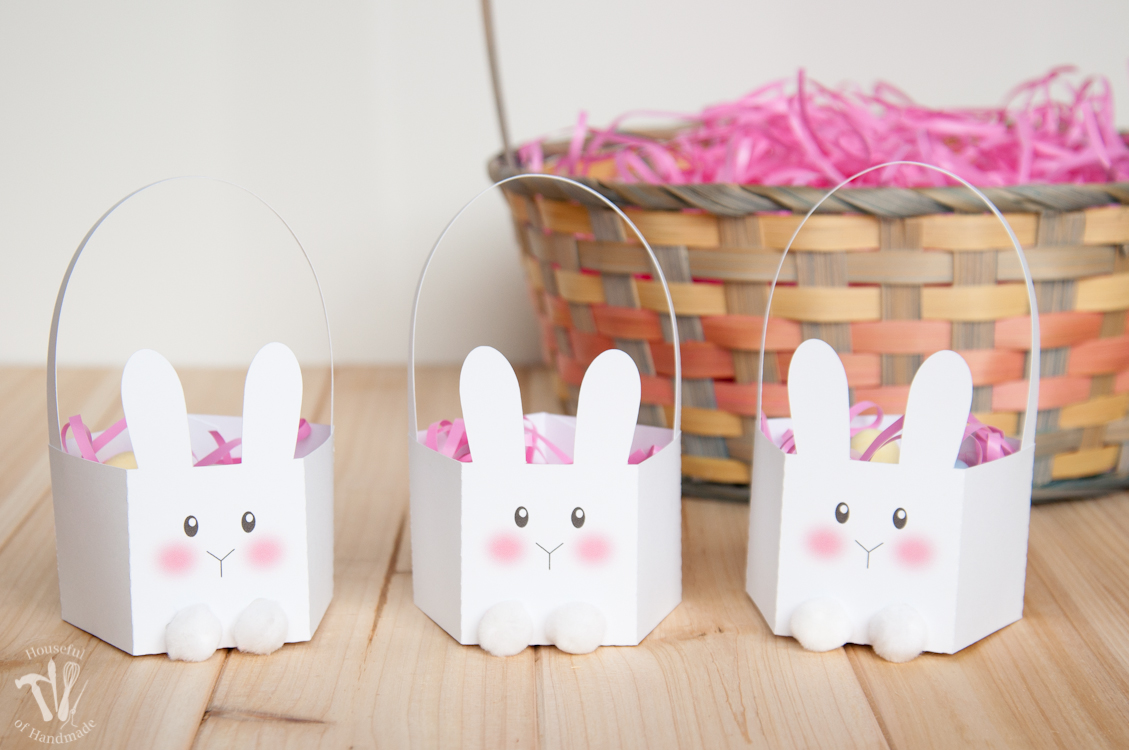 Three small bunny shaped easter baskets made out of paper in front of a large Easter basket.