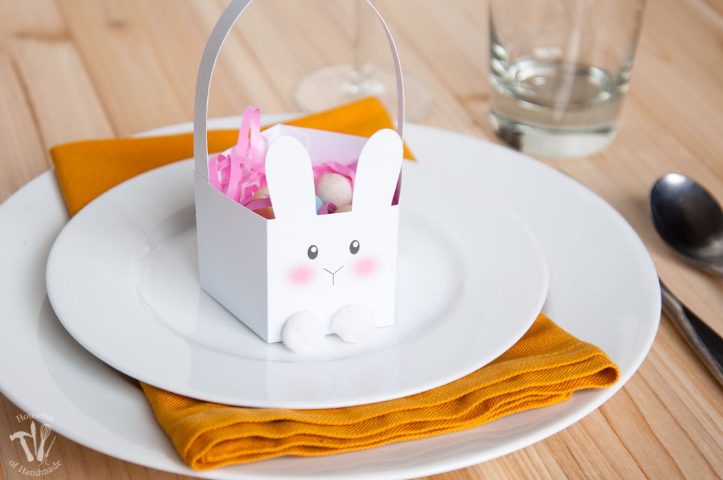Easter table set with white plates and yellow napkins with a paper Bunny basket holding candies on top.