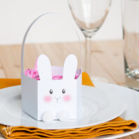 White paper bunny Easter basket with modern bunny face and pom pom feet.