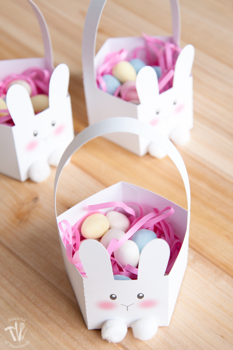 Three white bunny Easter baskets with pink Easter grass and easter egg candies inside.