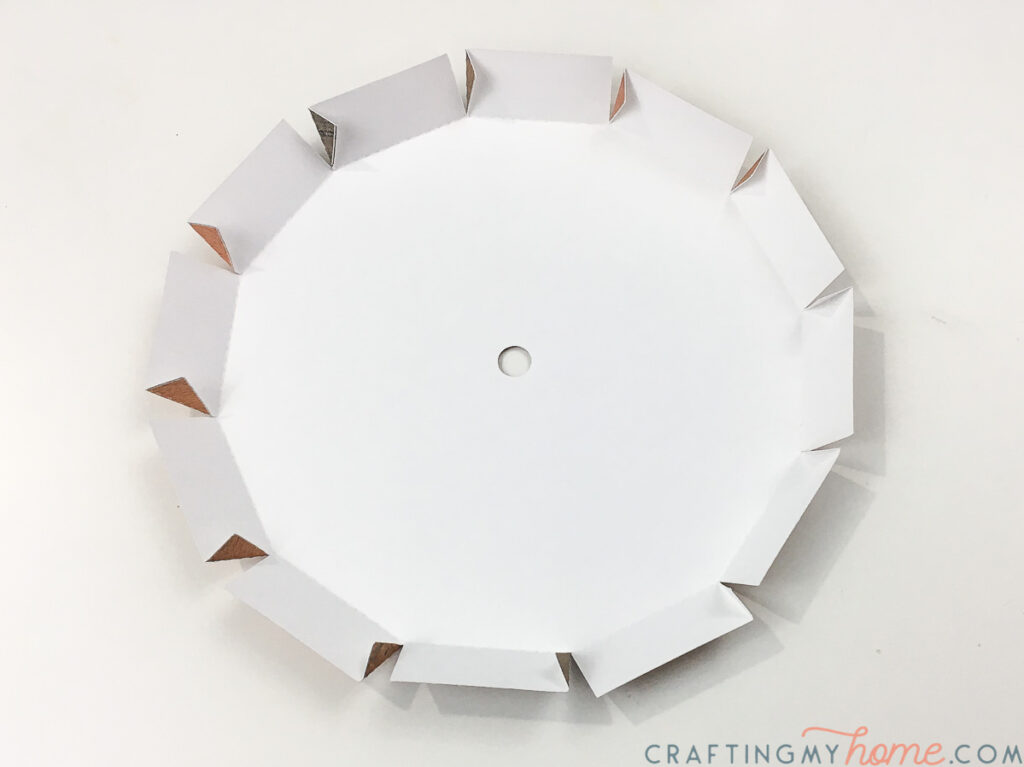 The center piece of the wall clock being folded.