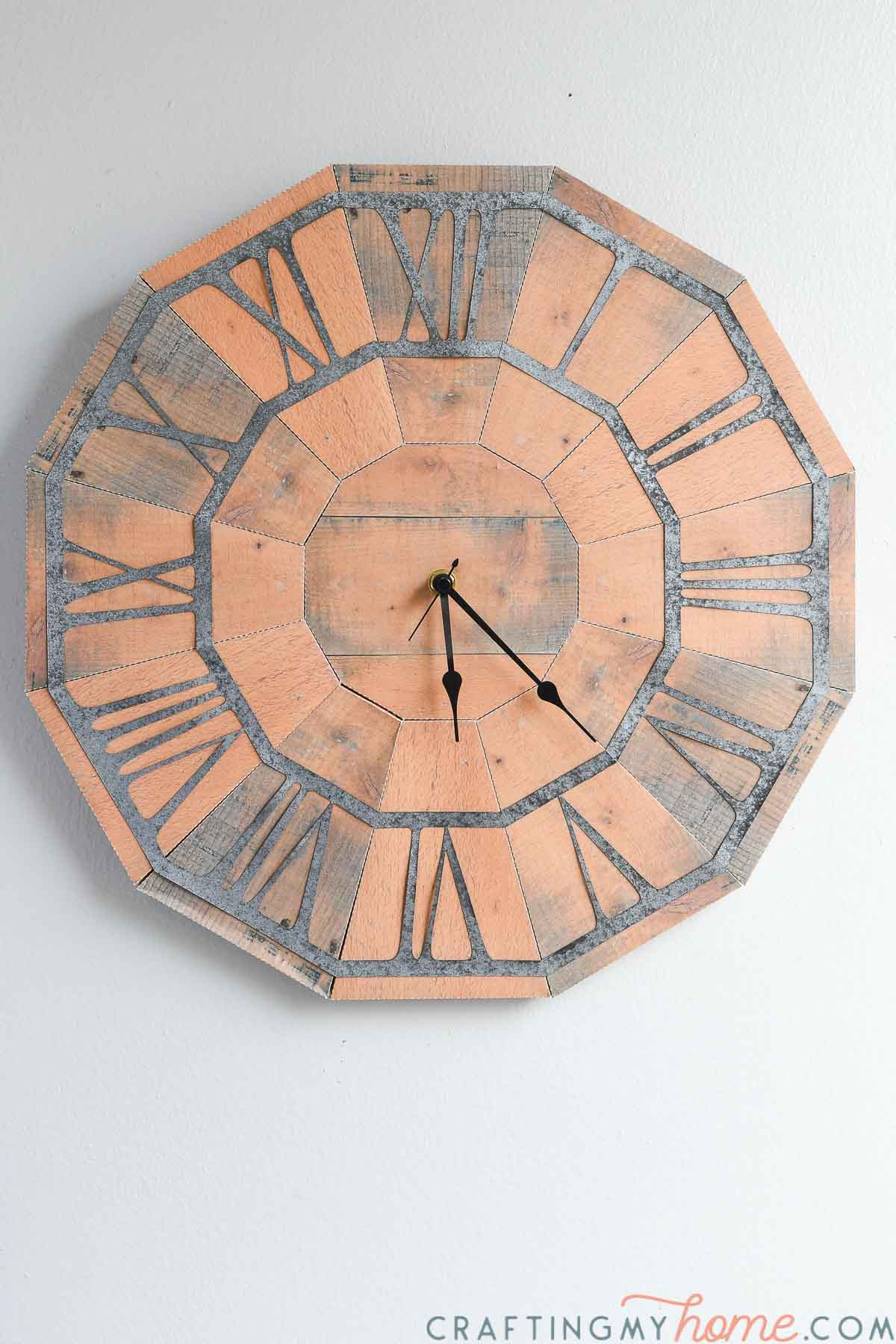 The completed pallet wood wall clock made from paper on the wall.