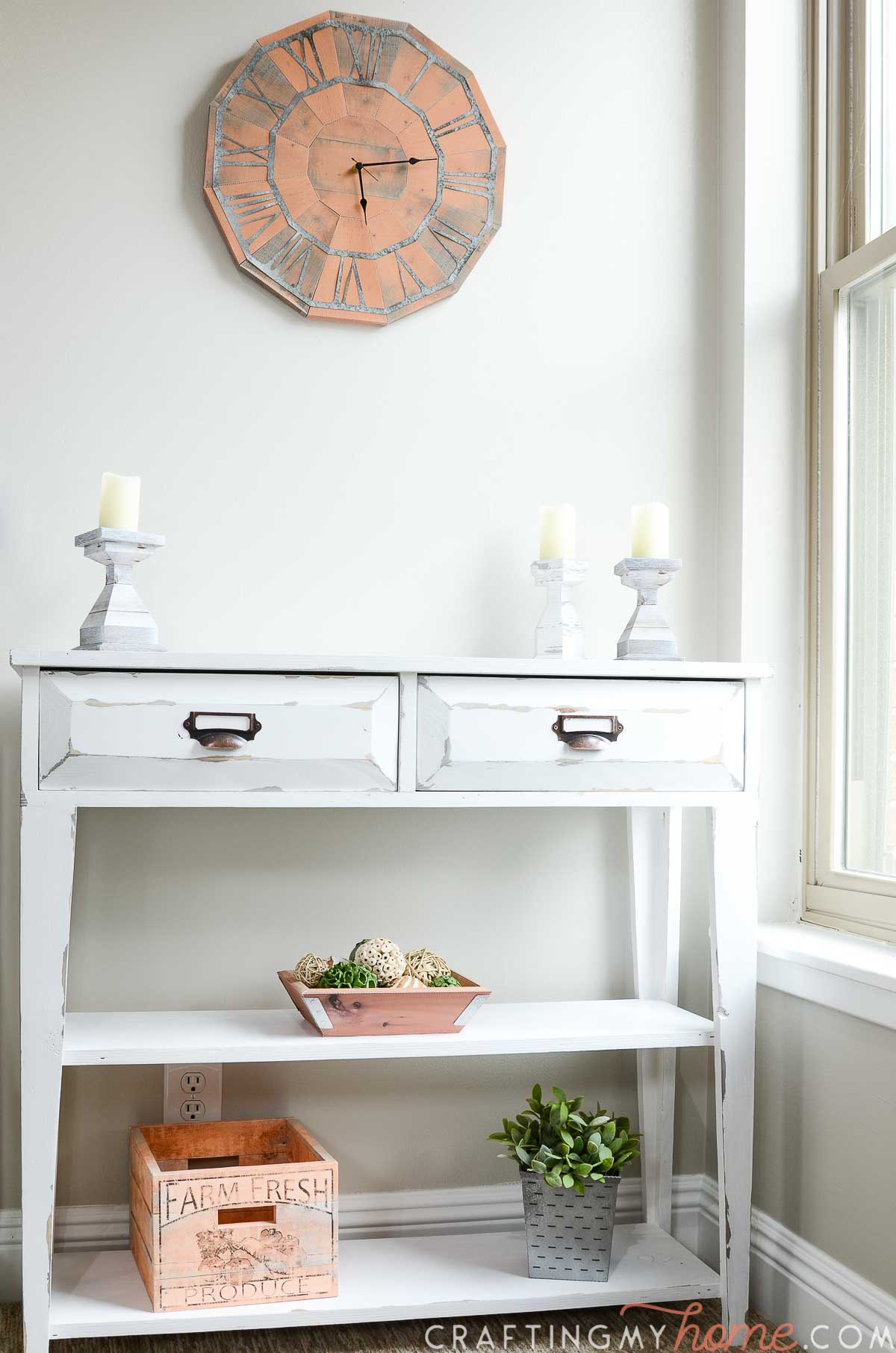 Small white console table with farmhouse decor on it and the paper wall clock hanging above it.