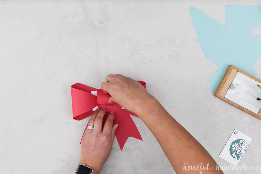 Red paper bow gift card holder being folded around an Amazon gift card.