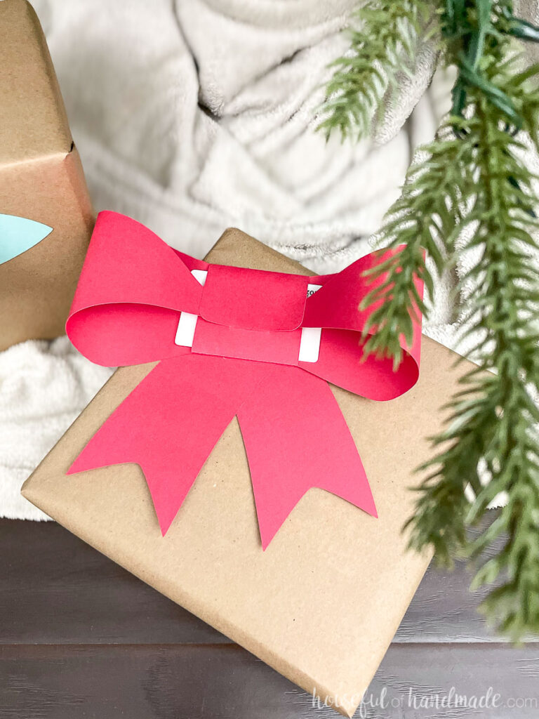 Christmas present under the Christmas tree with a red paper bow gift card holder on the front of it.