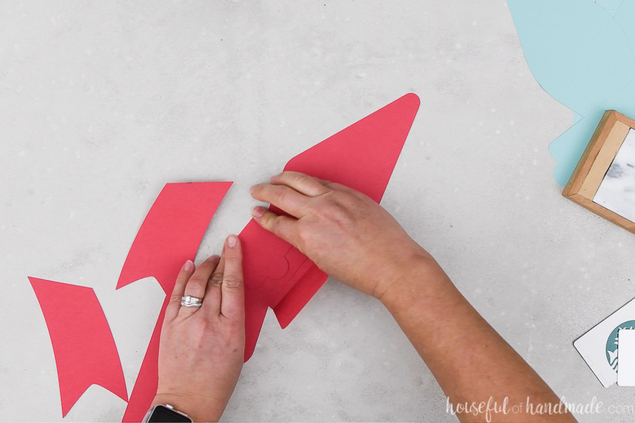 Folding the flaps on the paper bows cut out of red cardstock.