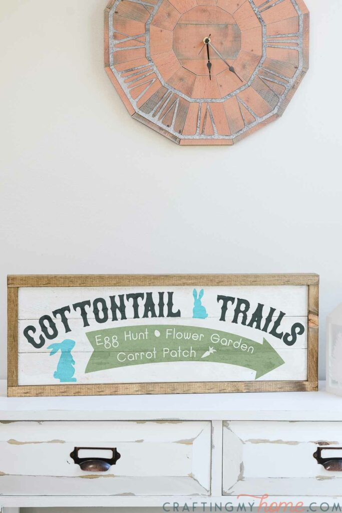 Farmhouse wood sign for Easter that says Cottontail Trails, Egg hunt, Flower garden, Carrot patch with an arrow and bunny silhouettes on it.