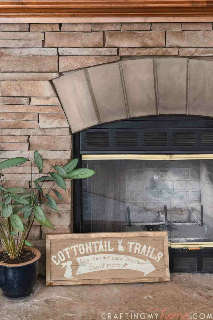 Brown stained wood sign for Easter on the hearth of a fireplace.