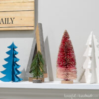 A variety of Christmas trees on the holiday mantel for decor.