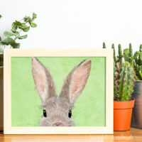 Horizontal bunny art in a frame next to potted plants.