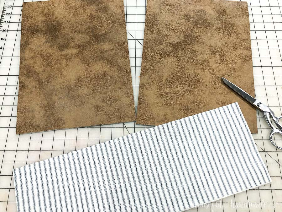 The leather and canvas pieces cut out to sew the decorative leather pillow.
