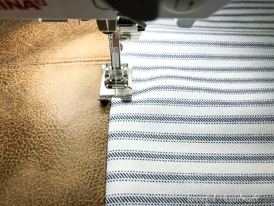 Sewing a top-stitch on the fabric side after adding it to the leather decorative pillow covers.