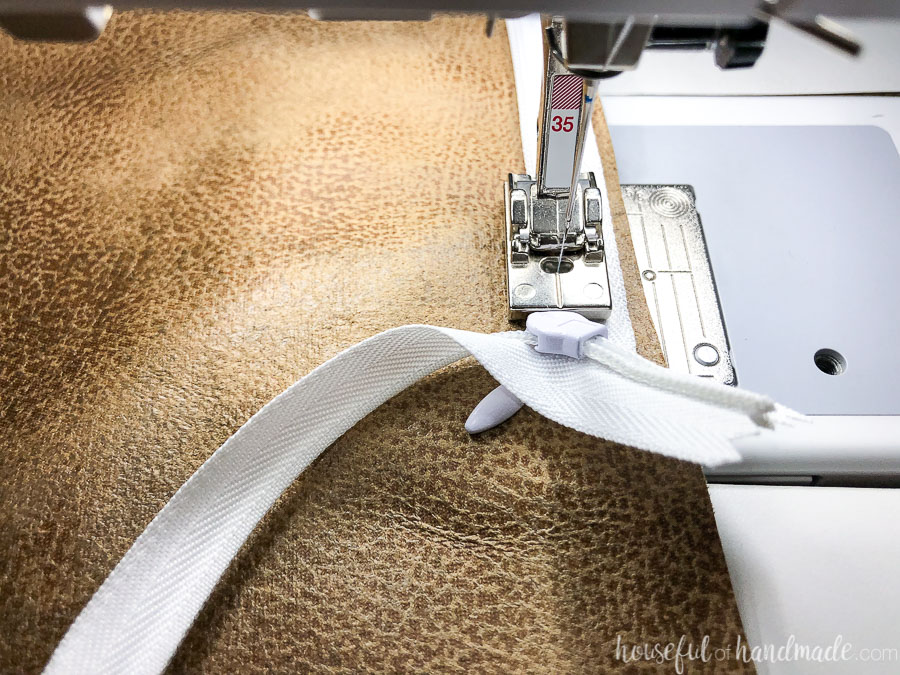 Close-up of sewing to the edge of the invisible zipper on the DIY pillow covers.