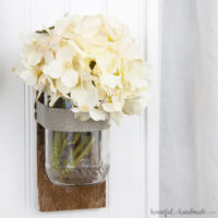 White flowers in a glass wall vase with reclaimed wood backing hanging on a wall.
