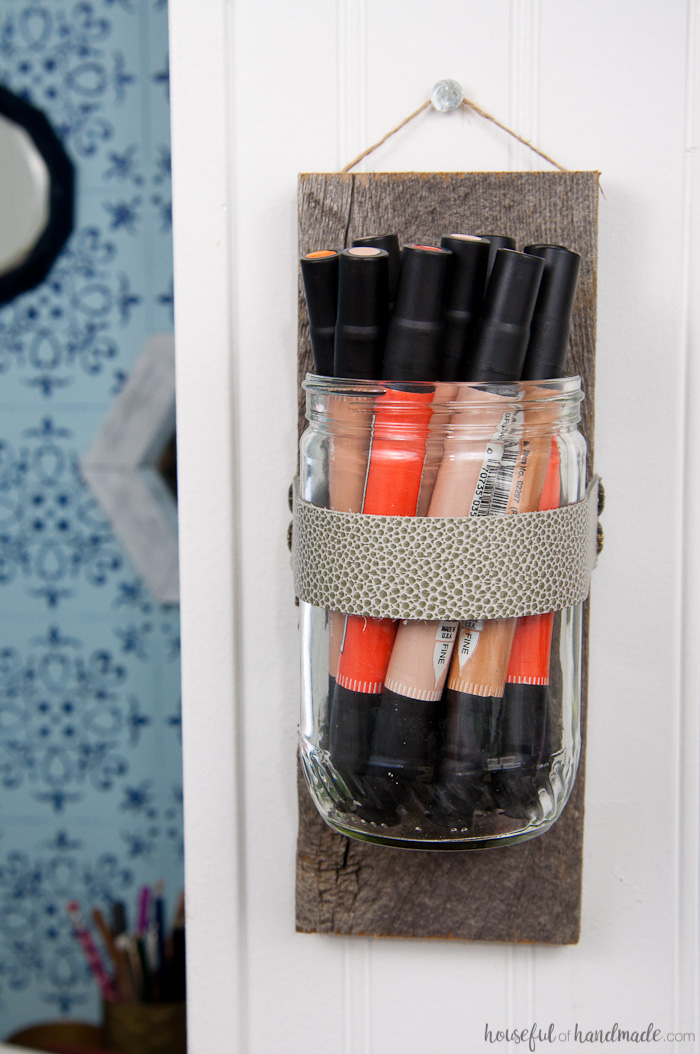 Recycled glass jar into a wall vase to hold craft supplies.