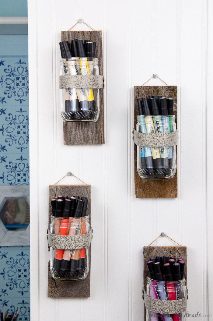 Close up of the simple glass wall vases holding markers in rainbow order hanging on a wall.