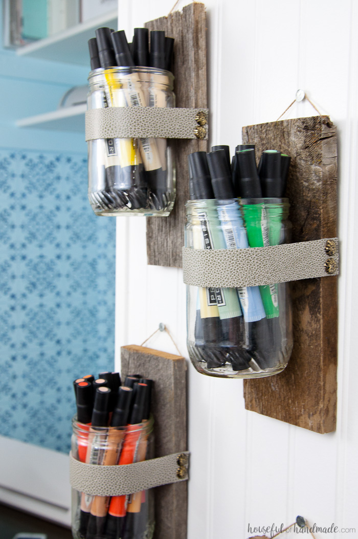 Organizing art markers in a rainbow inside the DIY wall vases hanging in the craft room.