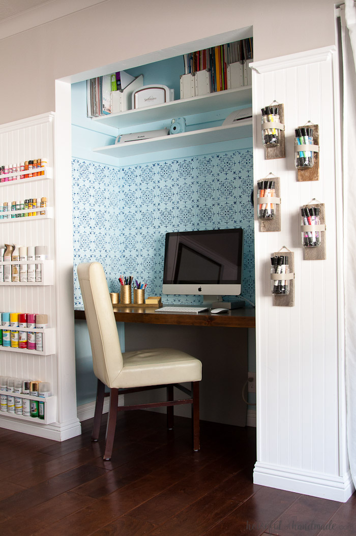 Desk in a closet with stenciled focal wall and wall vases on one side holding colorful markers and paint storage on the other side.