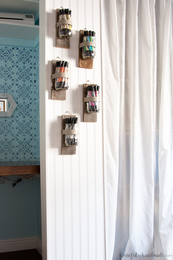 Five DIY wall vases made from old food jars and reclaimed wood on a wall holding craft supplies.