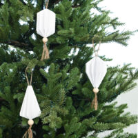 Three white paper Christmas ornaments in the shape of jewels with wood beads and tassels on the bottom.