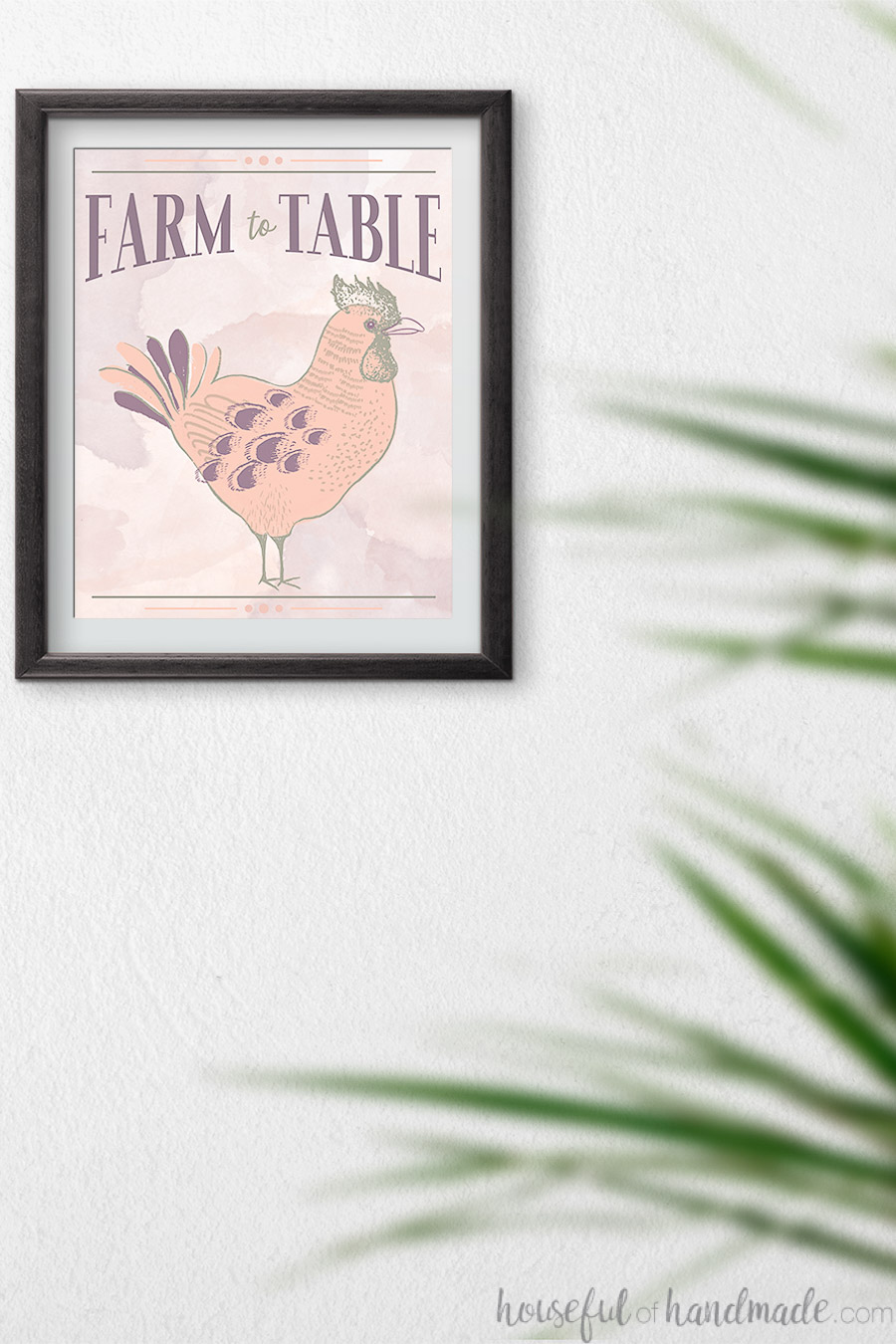 Farm to table spring printable hanging in a frame on the wall behind a plant.