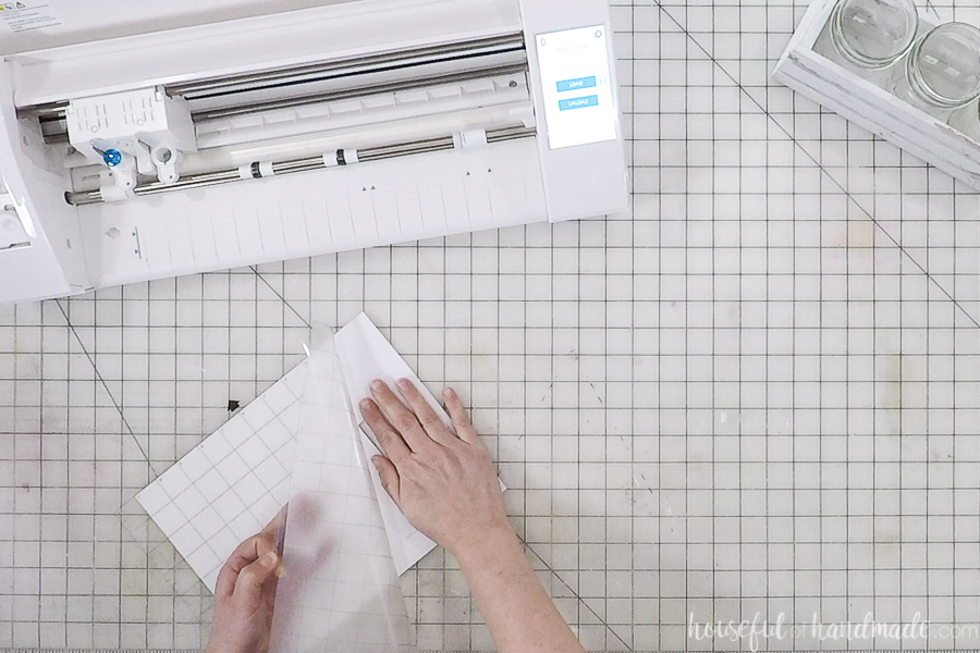 Removing cut out paper from the cutting mat in front of the Silhouette Cameo machine.