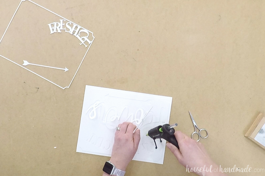Hot glueing the word flower to the backing while using the cut out paper as a template.