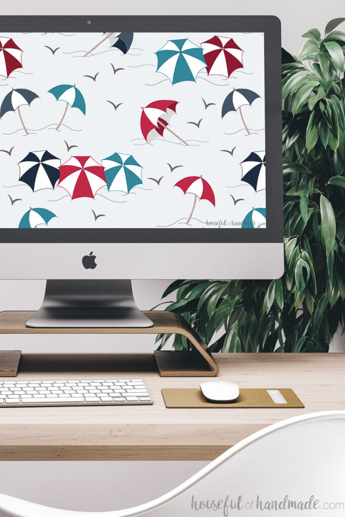 iMac computer with red, white and blue striped umbrella print digital wallpaper on the screen.