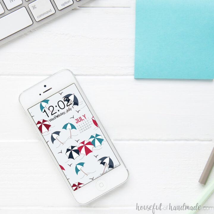 Smartphone on a desk with the red, navy and turquoise beach umbrella background as the home screen wallpaper.